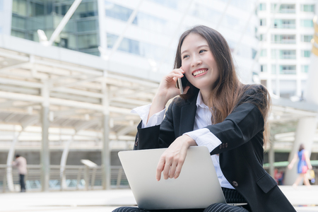 finding out: Young oung business woman smiling working with laptop out door,looking screen With gesture of rejoicing, shock, surprise happy emotion