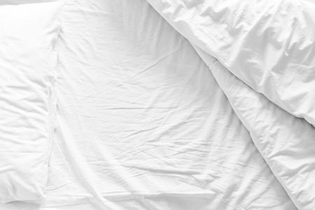 unmade bed with crumpled bed sheet, a blanket and pillows after comfort duvet sleep waking up in the morning.