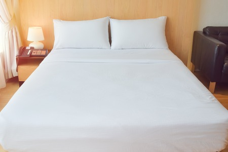 comfortable: comfortable white bed in the room for Comfortable furniture and clothes provide. Stock Photo