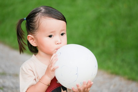 Blowing Up Balloon: Close up portrait of little girl blowing up a balloon in the green garden.