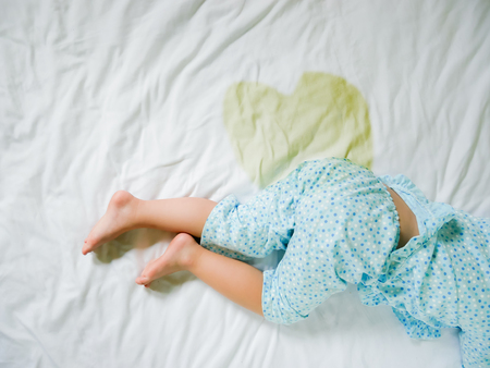 Bedwetting ,Child pee on a mattress,Little girl feet and pee in bed sheet,Child development concept ,selected focus at wet on the bed Foto de archivo