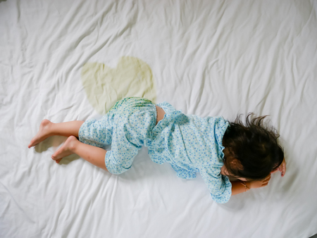 Bedwetting ,Child pee on a mattress,Little girl feet and pee in bed sheet,Child development concept ,selected focus at wet on the bed Archivio Fotografico