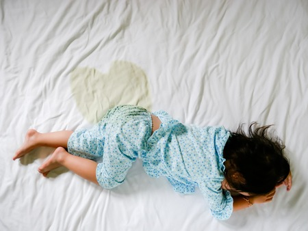Child pee on a mattress, Little girl feet and pee in bed sheet, Child development concept , selected focus. Foto de archivo