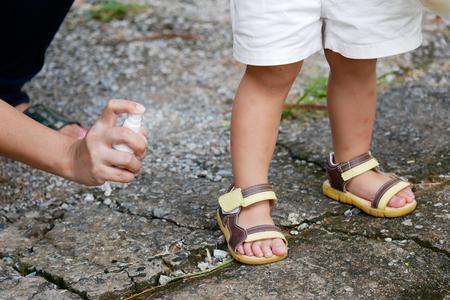 Moeder spuitend insect of muggenwerende middelen op het huidmeisje, muggenspray voor baby's, peuters die uw kinderen beschermen tegen muggen en andere insecten. Stockfoto - 85507108