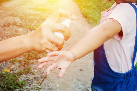 Madre spruzzando insetti o repellenti contro le zanzare sulla ragazza della pelle, repellente per zanzare per i bambini, i bambini che proteggeranno i vostri bambini da zanzare e altri insetti.