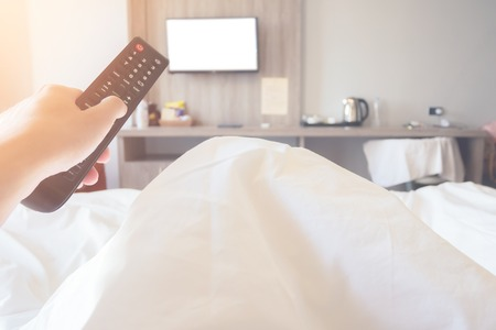 hand holding remote control television ob bed in bedroom close up