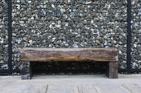 old wooden park bench decoration on stone wall ,Classic nature architecture furniture design Banco de Imagens