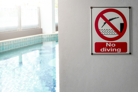 No diving sign at the poolside warning on blurred swimming pool