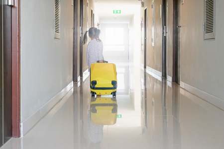 Children or little girl carrying luggage walking on the hallway at the hotel or hostels