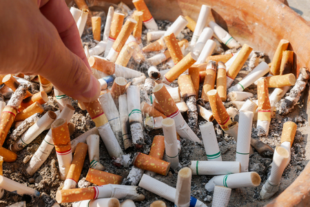 stop smoking today, hand putting out a cigarette butt on many cigarette butts for backgrounds Imagens