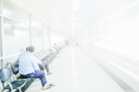 Abstract blurred people waiting in corridor hospital interior background with defocused effect.