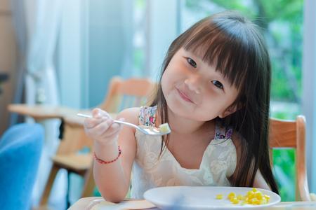 Kleines asiatisches Kindermädchen, das morgens mit einem glücklichen lächelnden Gesicht frühstückt und Essen auf einem Löffel zeigt. Standard-Bild