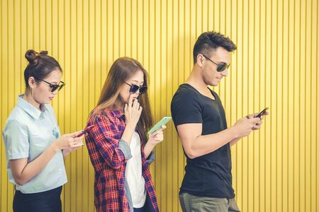 Group of young friends using smart phone against yellow wall ,people addicted by mobile smartphone concept 版權商用圖片