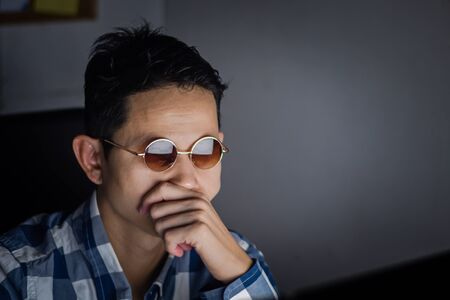 Business man having serious and contemplative after viewing the summary chart of the companys report at office at over night time