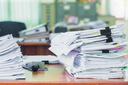 Heap of papers work stack documents on office desk ,business documents billing and examination to report the summary results annual report for presented. Business offices concept
