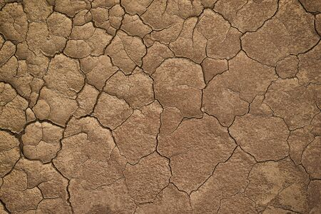 Dry cracked earth during in a rainy season because lack of rain shortage of water.cracked soil texture
