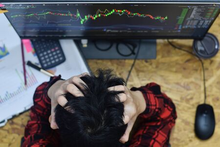 Fatigue man hands holding the head because of stress and having a headache at home office in while trading forex or stocks market online investment at night time