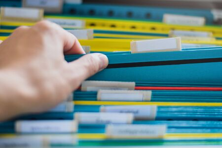 Closeup of a hand search and select a file folder from a group of file folders on shelves in an office