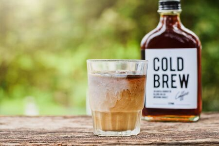 Cold brew coffee with milk on a table outside with cold-brew coffee in a glass bottle for take away 版權商用圖片