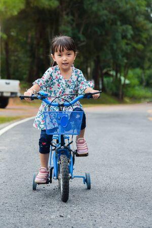 Children little girl are ride bike on road