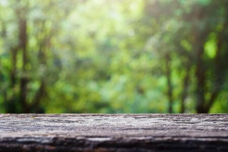 old wooden table top on green blurred abstract background from foliage background. Ready used us display or montage products design