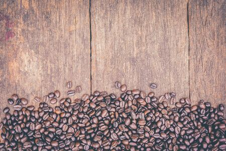 Coffee beans on old grunge wood table for background