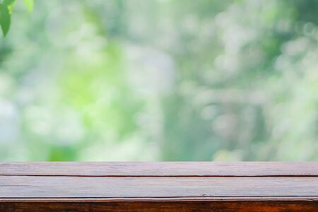 Empty wooden deck table top on green blurred abstract background from foliage background. Ready used us display or montage products design