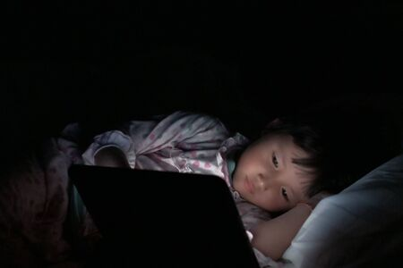 liitle girl are watching tablets in bed at night, children using phones or playing tablet games, children using games with addiction and cartoon concepts