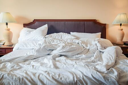 Unmade bed with crumpled bed sheet, a blanket and pillows after comfort duvet sleep waking up in the morning with lamp