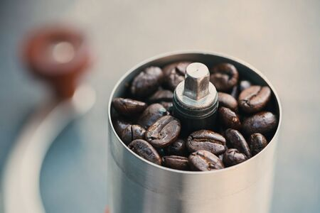 Coffee beans in a hand grinder, closeup roasted coffee beans into a manual coffee grinder Stock fotó