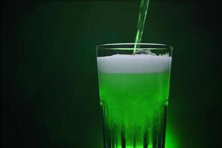 Pour Green Beer in beer glass on dark background at night ST patricks day party with copy space for you advertising design backdrops.