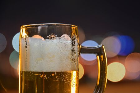 cold beer in a colorful summer night party ,close up beer mug on night light bokeh background.