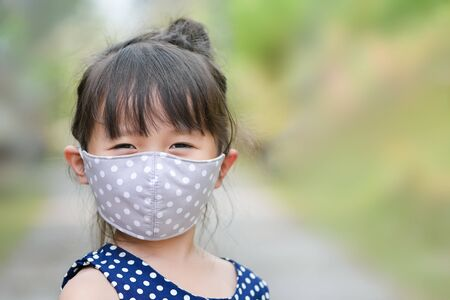 Little girl has fabric mask protect herself from Coronavirus COVID-19,hand stop sign when child leave the house,,child with a mask on her nose for safety outdoor activity,illness or Air pollution