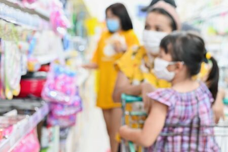 Blurred supermarket with unidentified mother daughter has fabric mask protect herself from Coronavirus when go to supermarket after supermarket open again After covid-19 outbreak,for safety healthcare