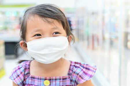 Little girl has fabric mask protect herself from Coronavirus when child go to supermarket with mother after supermarket open again ,child with a mask on nose for safety outdoor public place activity