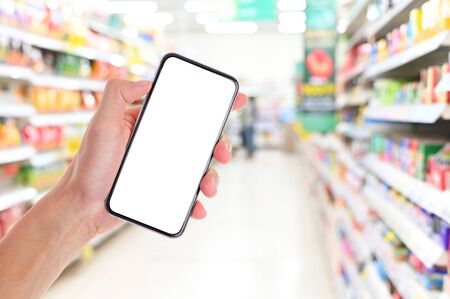 Man hand holding smartphone in supermarket ,Empty white screen smartphone for design advertising on mobile phone screen ezy replace with clipping path.