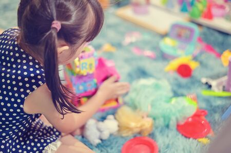 Close up Child little girl play toys disorderly mess in living room a dirty or untidy state of toy and doll at home.