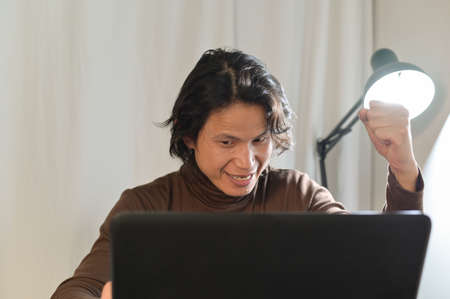 Asian business man looks very surprised at his laptop ,sitting looking at some unbelievable news at laptop screen and surprised gesturing successful at home office night time