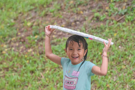 little Asian child girl playing in rainy day with laughing smile face