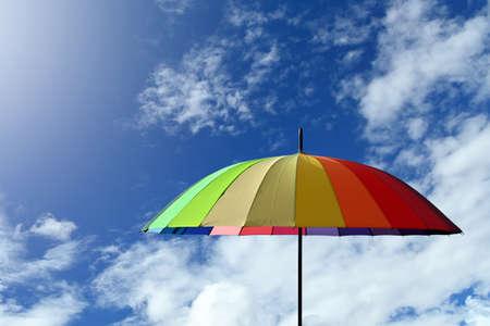Colorful umbrella multicolored on a blue sky background Archivio Fotografico