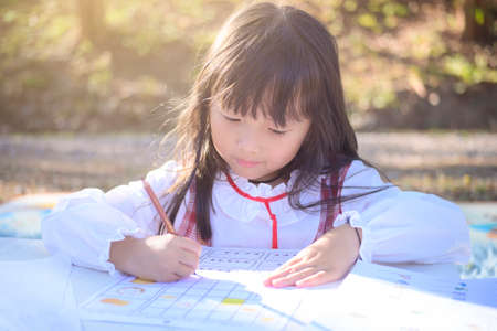 asian little girl lying drawing or made homework in the paper book for preschool kids in the home garden park