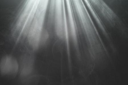 Illuminated gold spotlight rays on stage on black background for overlay design 版權商用圖片