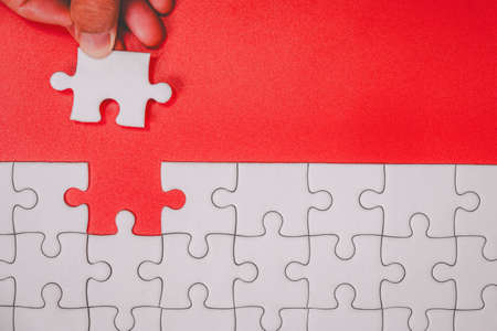 Human finger touching unfinished white jigsaw puzzle pieces on red background for finish goal