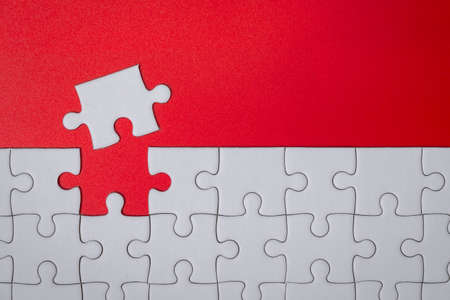 unfinished white jigsaw puzzle pieces on red background for finish goal 版權商用圖片