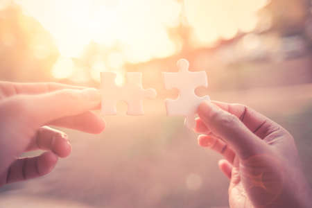 Close Up hand of man and woman connecting jigsaw puzzle with sunlight affect, Business solutions partnership success and strategy concept