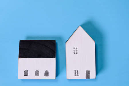Close-up of wooden miniature house model on blue background symbol of new house concept