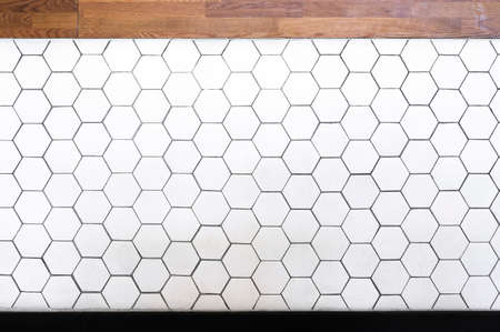 simple white hexagonal wall tiles and wooden texture pattern of hexagons as a background