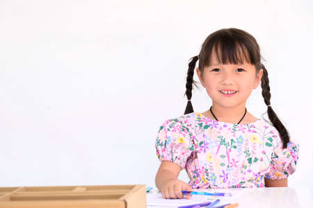 asian little girl lying drawing or made homework in the paper book for preschool kids in the home white wall