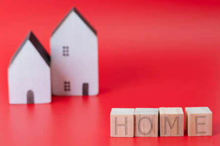 Close-up of wooden home text block with miniature house model on blue background symbol of new house concept