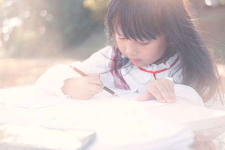 asian little girl lying drawing or made homework in the paper book for preschool kids in the home garden park with sun ligh flare
